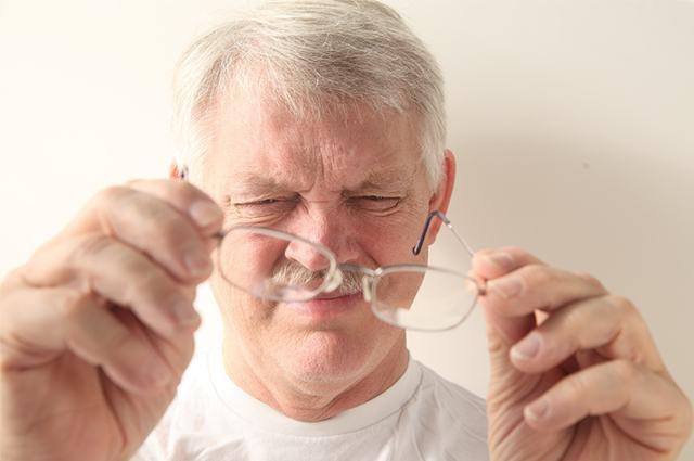 imagem-de-homem-fechando-os-olhos-e-segurando-oculos